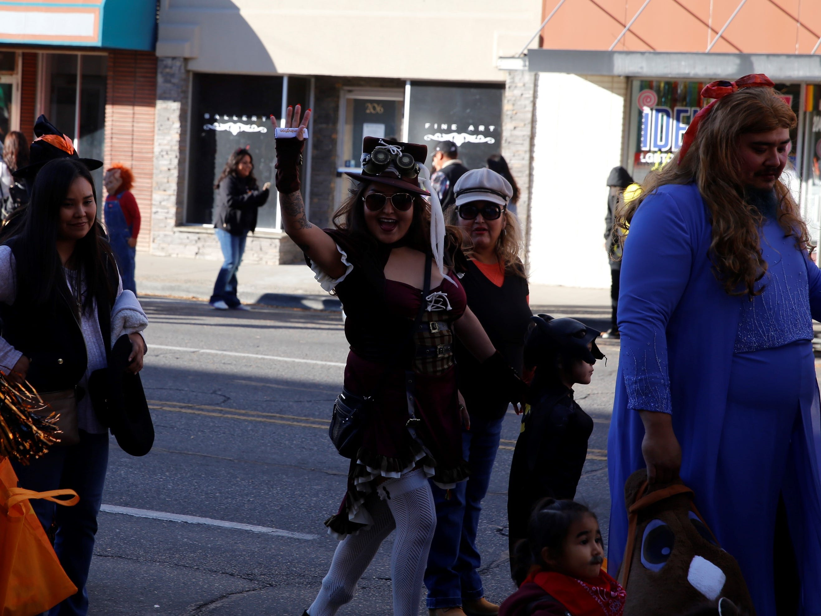 Sondra Etsitty, dressed in a 1920's Victorian era Steampunk outfit, waves while walking down Main Street during BooPalooza Wednesday in Farmington.