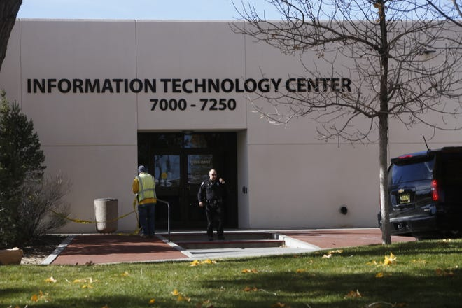 A Farmington police officer and a San Juan College employee clear the Information Technology Center building to allow students and staff members back in after a suspicious device was found Thursday morning in a restroom.