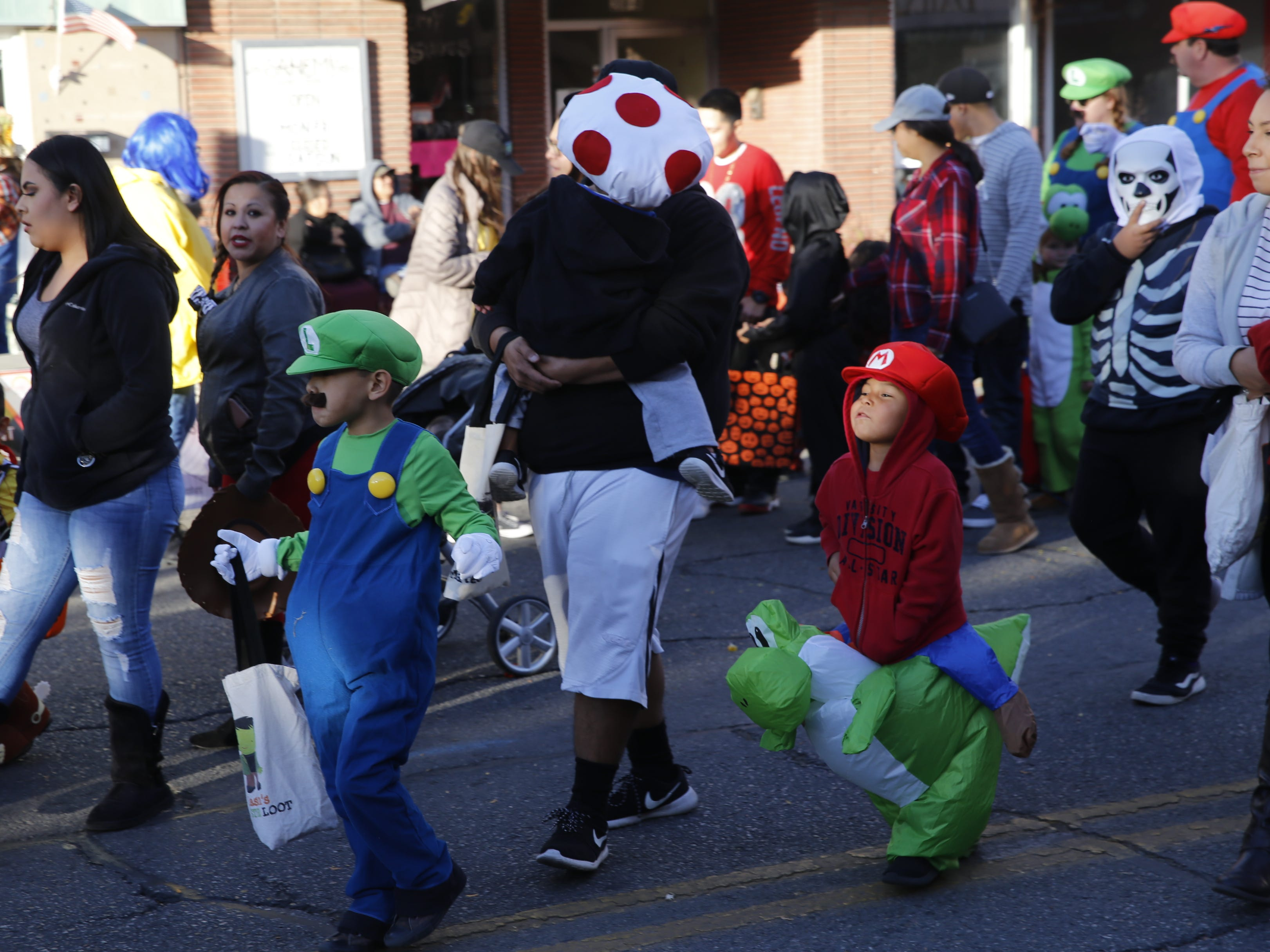 Trick or treaters walk down Main Street during PooPalooza Wednesday in Farmington.