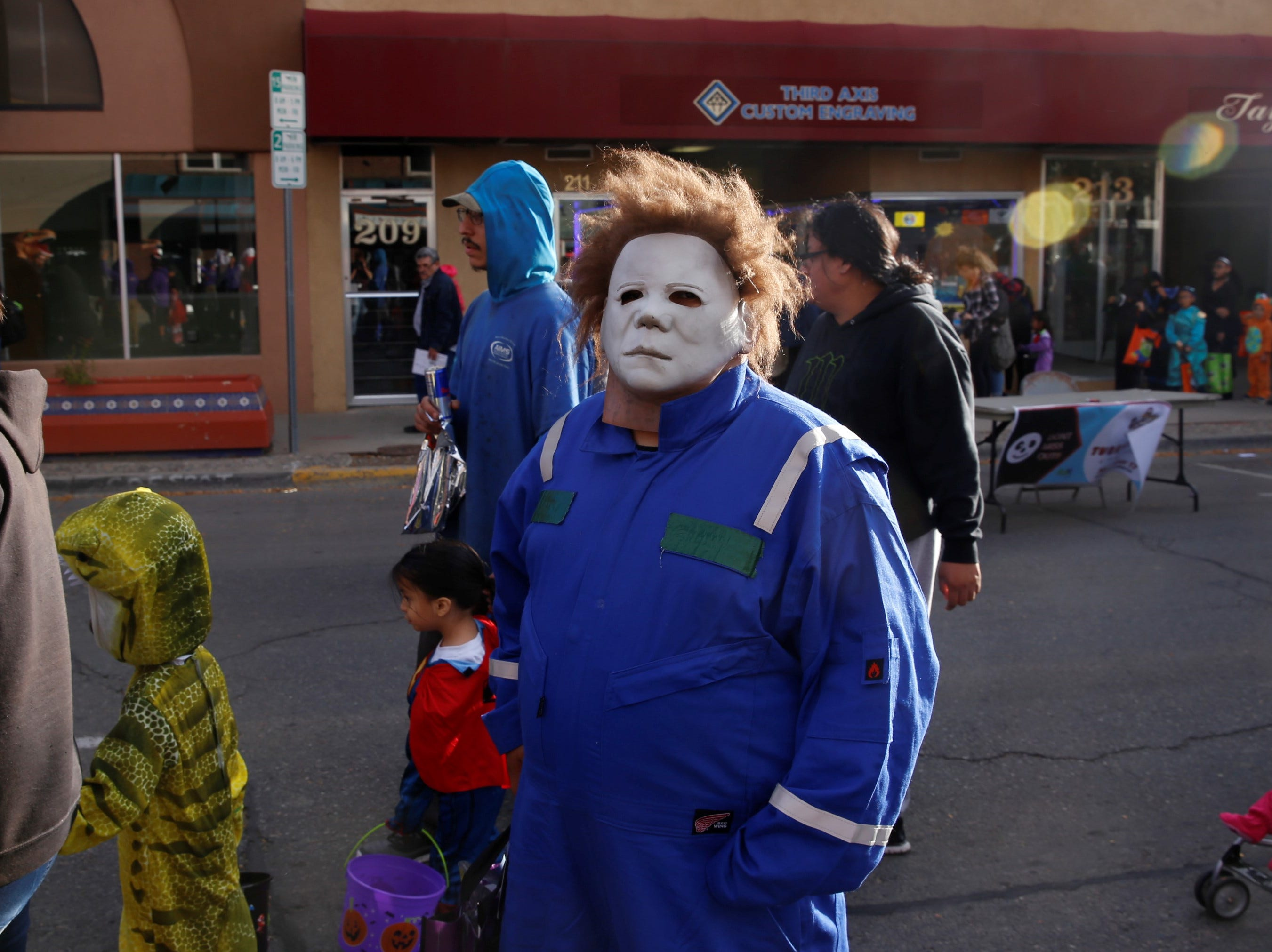 "Lydell Toledo, dressed as Michael Myers from ""Halloween,"" waits in line for candy on Main Street during BooPalooza Wednesday in Farmington."