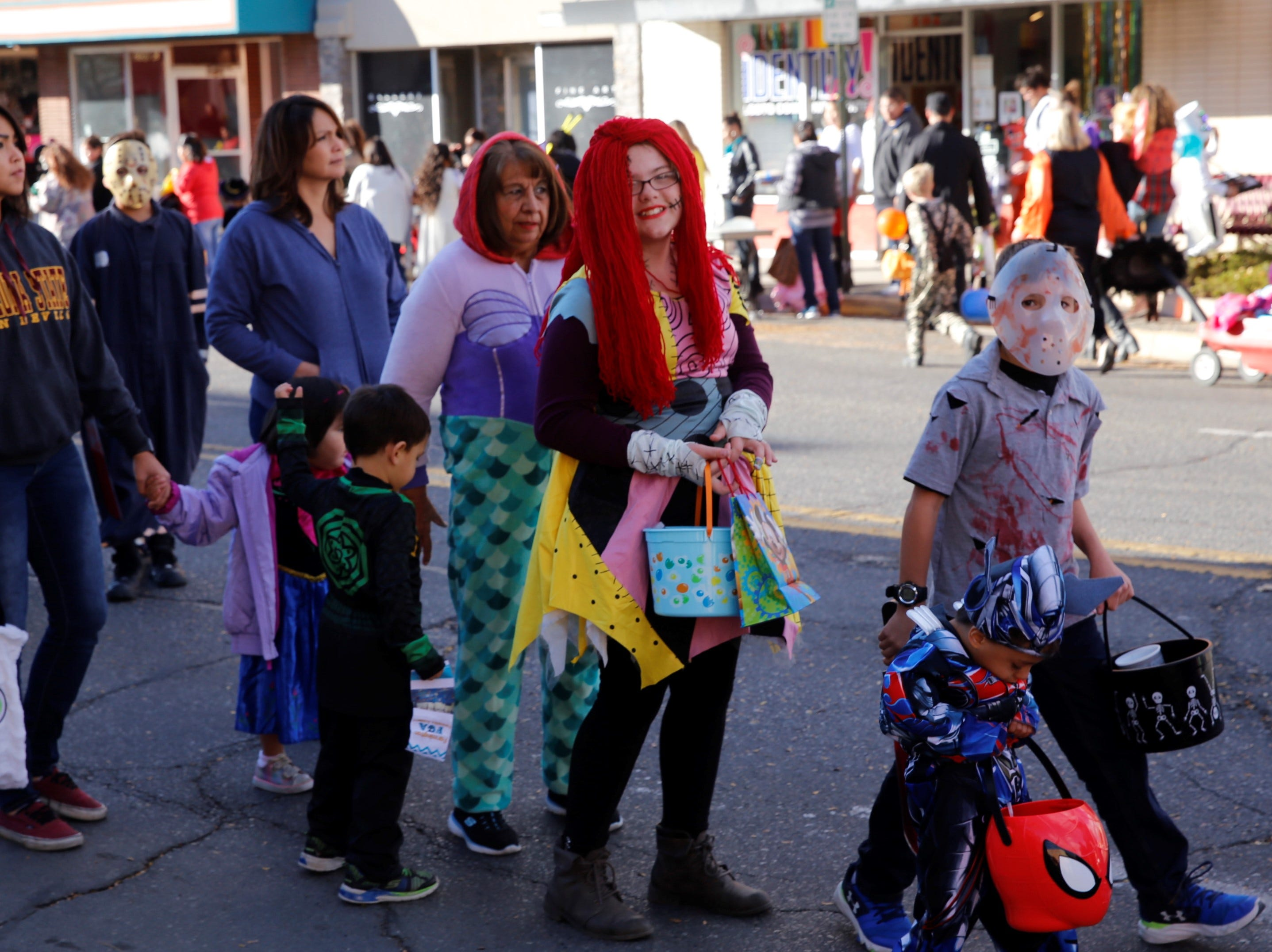 "Andrea Deal, in the center dressed as Sally from ""The Nightmare before Christmas,"" waits in line for candy on Main Street during BooPalooza Wednesday in Farmington."