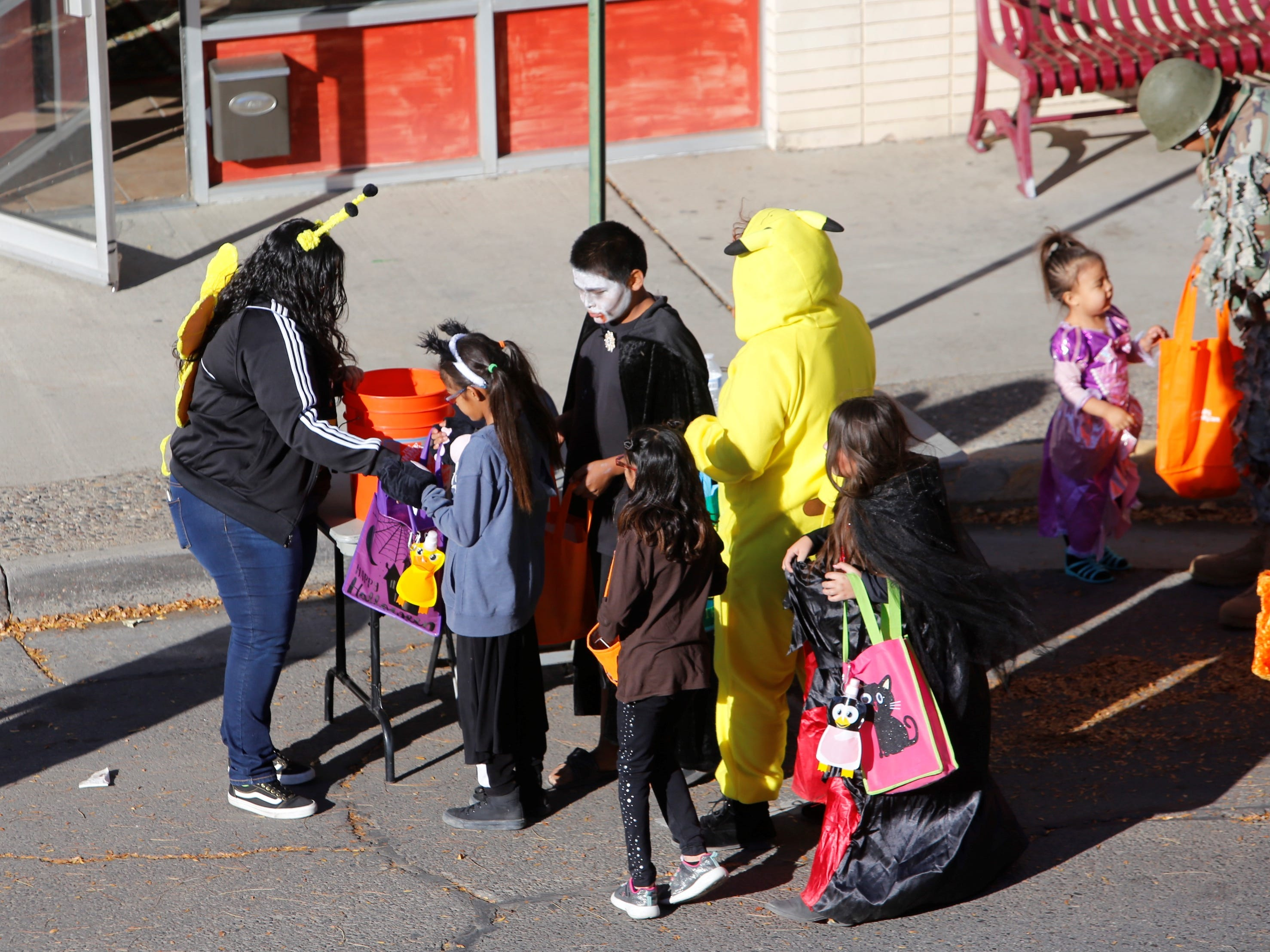 Trick or treaters line up to get candy walking down Main Street during BooPalooza Wednesday in Farmington.
