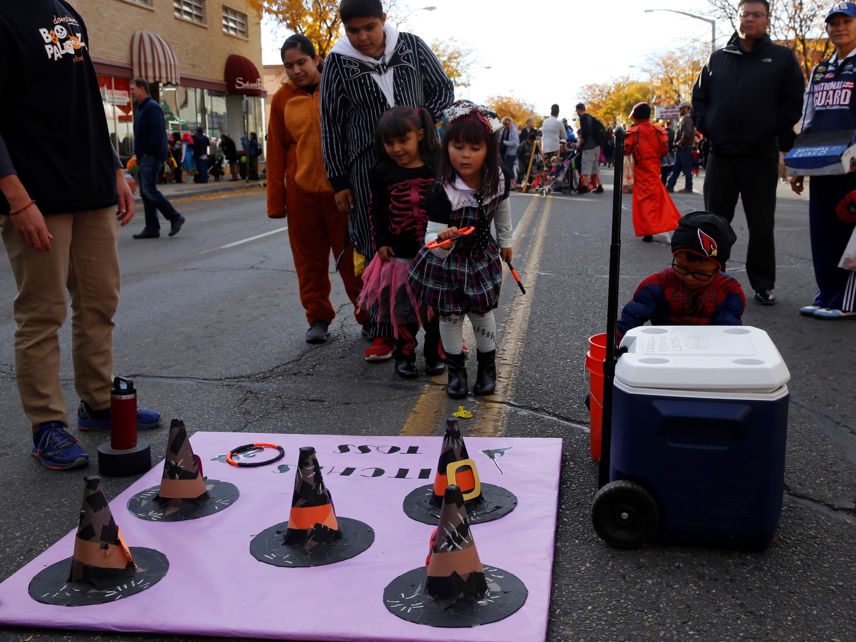 "Ximena Medrano, dressed as Frankie Stein of the ""Monster High"" fashion doll franchise, plays the game ""witches toss"" on Main Street during BooPalooza Wednesday in Farmington."