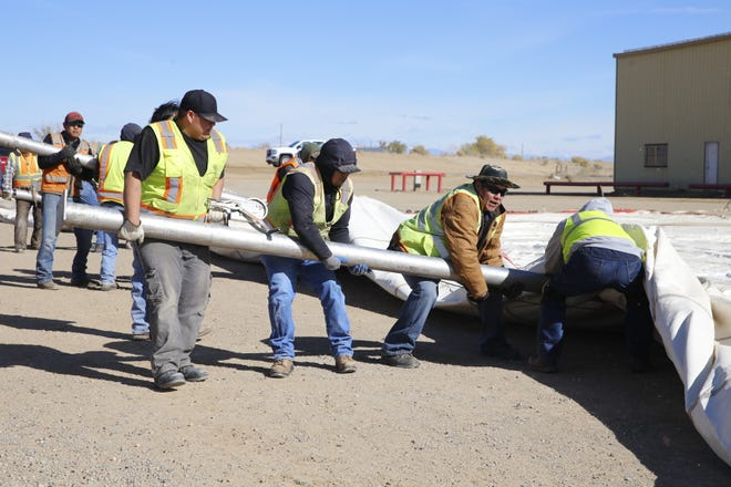 Navajo Agricultural Products Industry employees set up a large tent on Thursday as part of preparation work for the company's annual Customer Appreciation Day on Saturday.