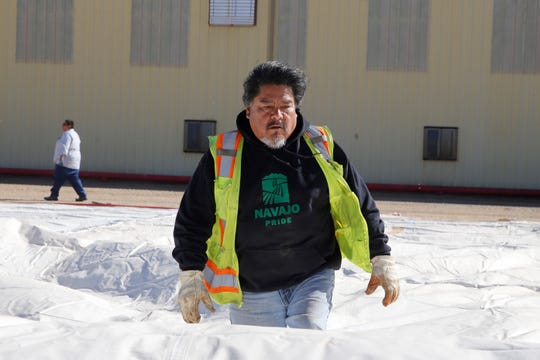 Equipment operator Robert Nargo helps unroll a tent on Thursday at the Navajo Agricultural Products Industry Region 2 Complex south of Farmington.