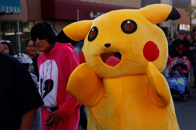 "Poncho Thomas, dressed as Pikachu from ""Pokemon,"" walks down Main Street during BooPalooza Wednesday in Farmington."