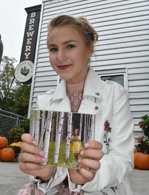 Aspen Jacobsen proudly displays her music CD during a release event at River's Edge Brewery in Milford.
