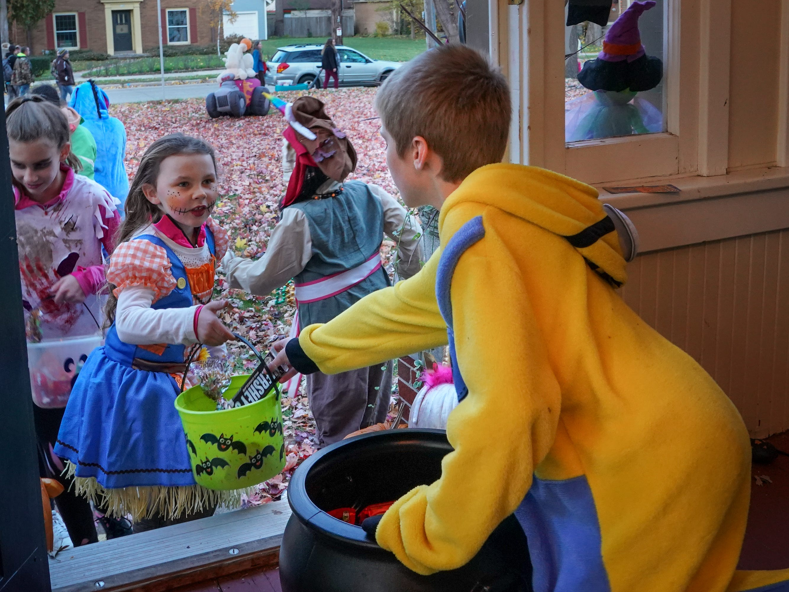 Titus Schroeder hands out candy to a group of trick or treaters. Children, along with their parents, made the most of the beautiful autumn weather to trick or treat in Oshkosh Wednesday evening.