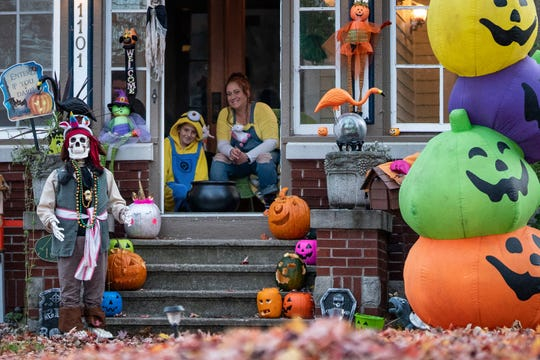 Titus Schroeder and his mother wait on their Merritt Avenue porch for trick-or-treaters.