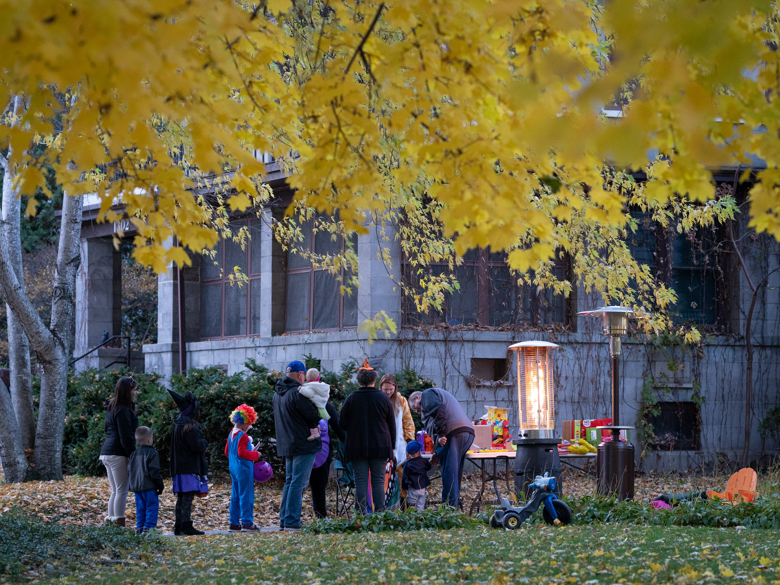 Dave Bayer and Makenzie Reinke hand out candy on Washington Avenue.  Children, along with their parents, made the most of the beautiful autumn weather to trick or treat in Oshkosh Wednesday evening.