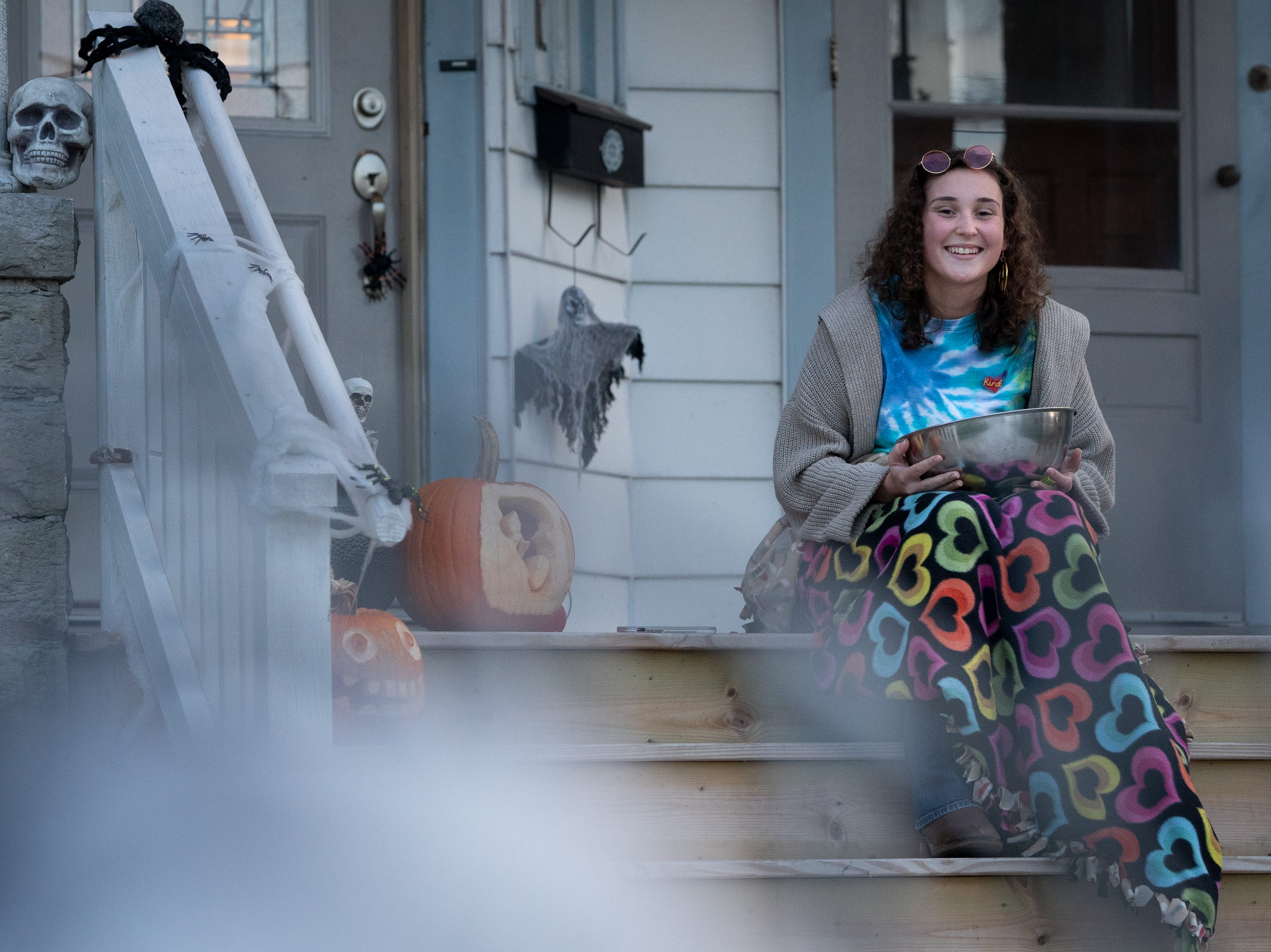 Cora Strand waits on the porch with candy for trick or treaters. Children, along with their parents, made the most of the beautiful autumn weather to trick or treat in Oshkosh Wednesday evening.