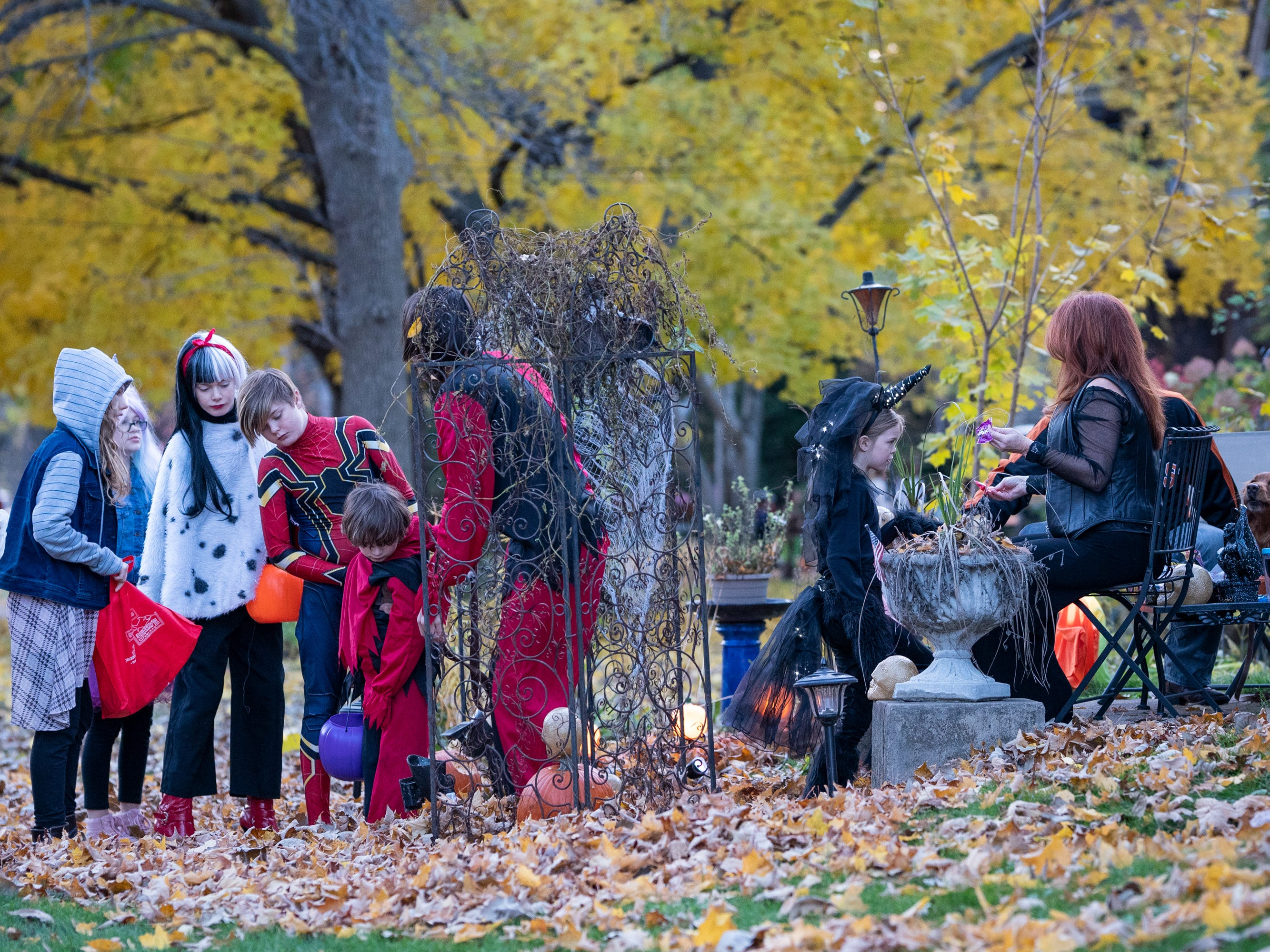 Jeff and Lainey Schinker hand out candy in front of their house on Washington Avenue. Children, along with their parents, made the most of the beautiful autumn weather to trick or treat in Oshkosh Wednesday evening.