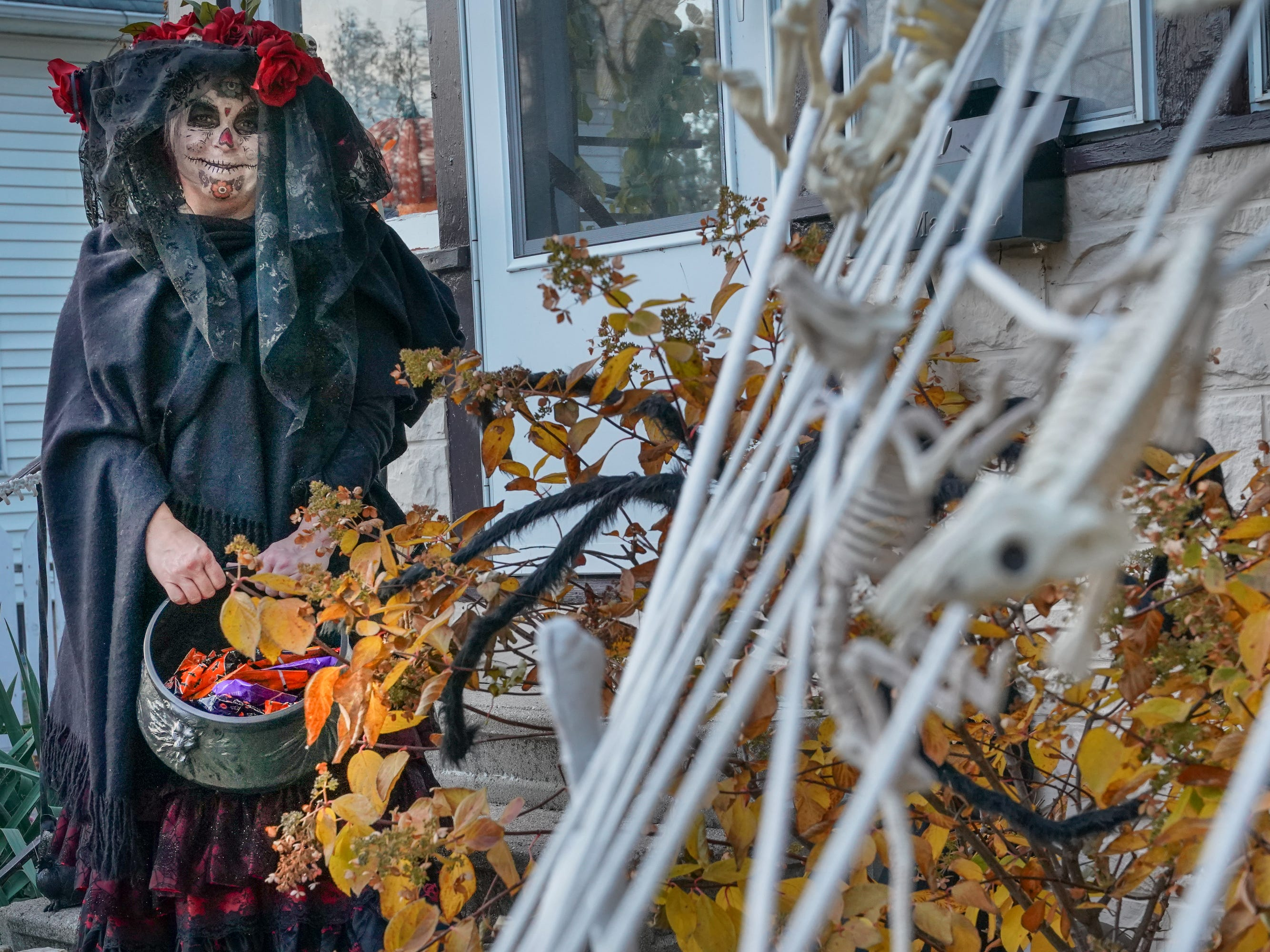 Jennifer Mansavage waits in front of her house for trick or treaters. Children, along with their parents, made the most of the beautiful autumn weather to trick or treat in Oshkosh Wednesday evening.