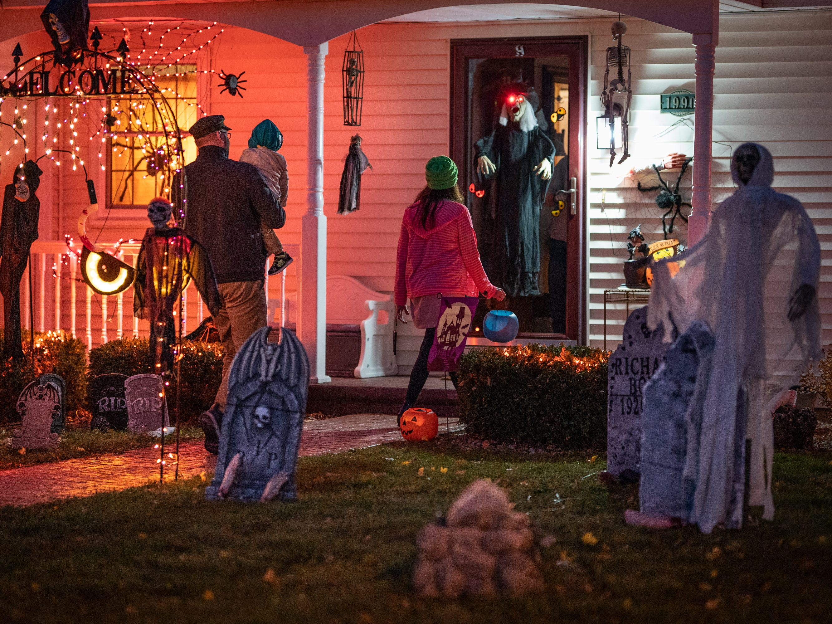 Mathew Hlinak and Amber Reid take son David to a decorated house on South Westhaven Drive. Children, along with their parents, made the most of the beautiful autumn weather to trick or treat in Oshkosh Wednesday evening.