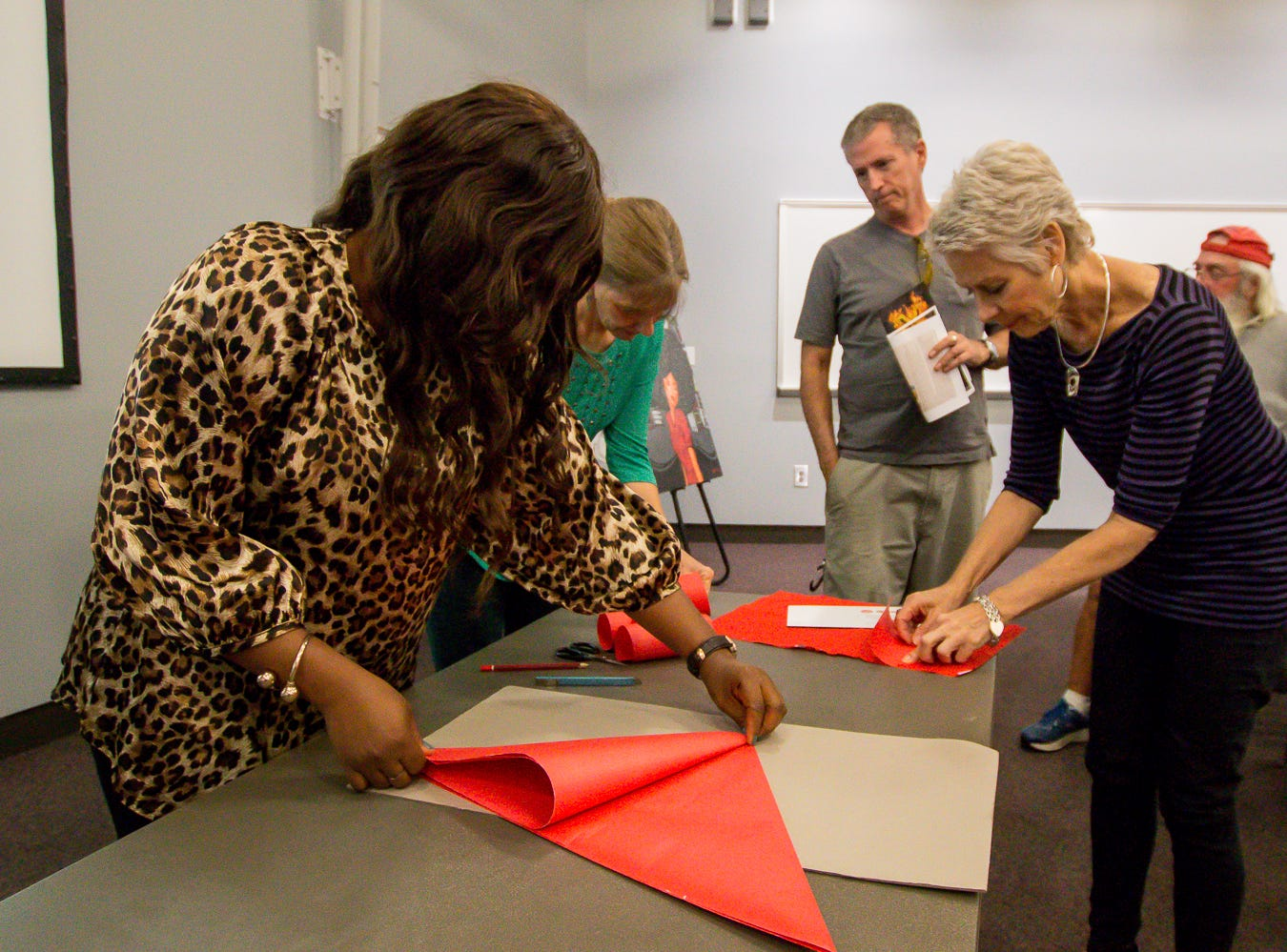 The Great Gulfcoast Arts Festival's Invited International Artist Abigail Nnaji, of Abuja, Nigeria, left, demonstrates how she uses the Chinese paper cutting technique during a presentation in the Anna Lamar Switzer Building at Pensacola State College on Tuesday, October 30, 2018.