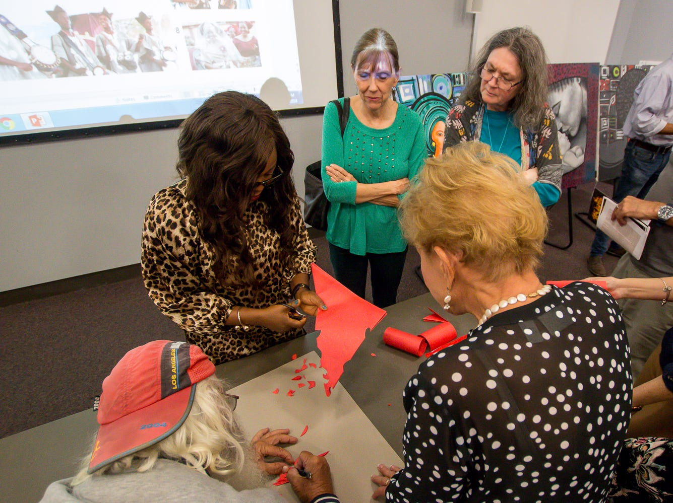 The Great Gulfcoast Arts Festival's Invited International Artist Abigail Nnaji, of Abuja, Nigeria, top left, demonstrates how she uses the Chinese paper cutting technique during a presentation in the Anna Lamar Switzer Building at Pensacola State College on Tuesday, October 30, 2018.