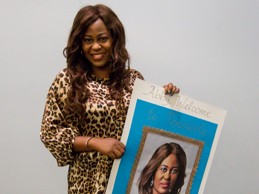 The Great Gulfcoast Arts Festival's Invited International Artist Abigail Nnaji, of Abuja, Nigeria, poses with a signed gift from the GGAF before her presentation in the Anna Lamar Switzer Building at Pensacola State College on Tuesday, October 30, 2018.