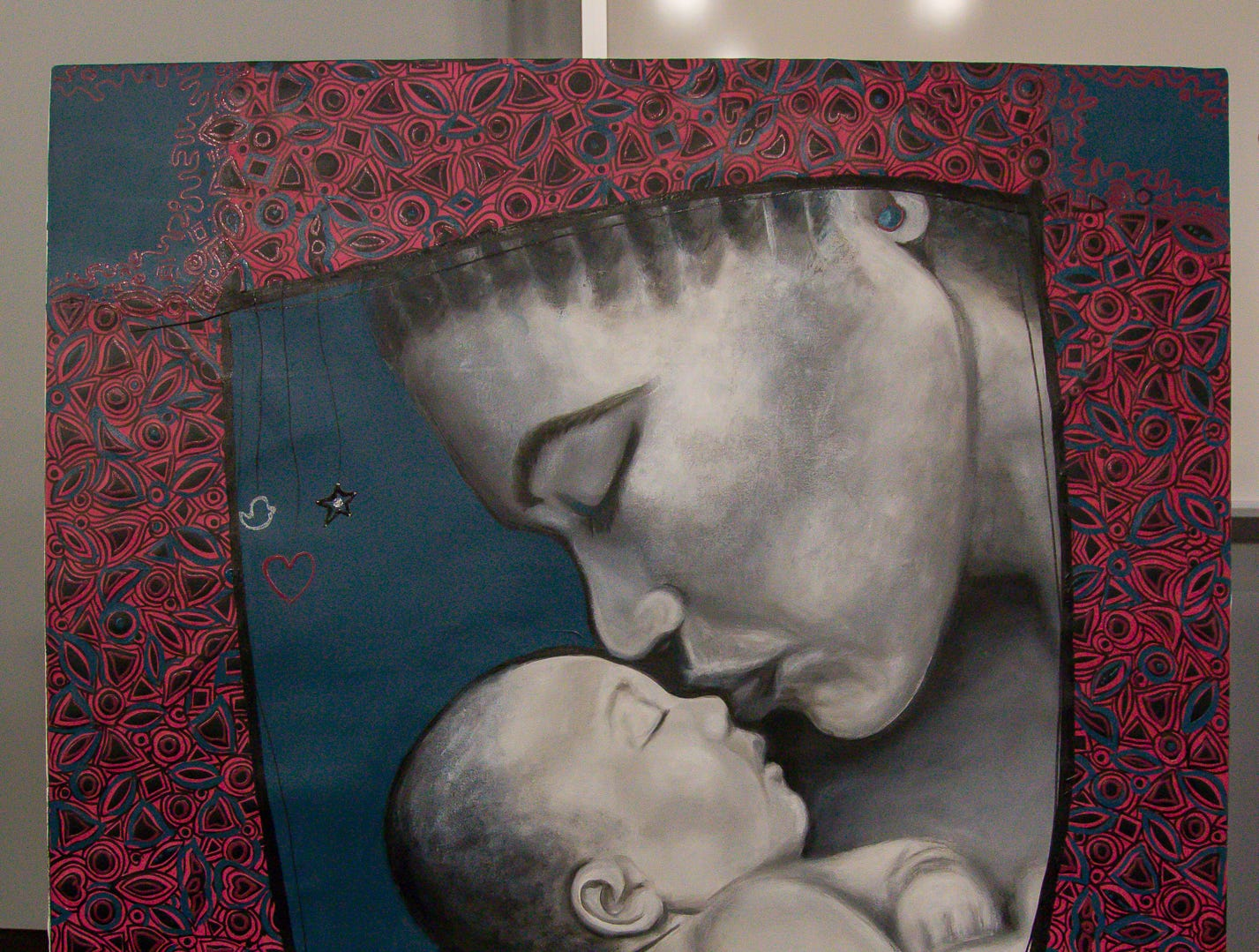 "Abigail Nnaji's ""Motherly Love"" is shown during a presentation on her mixed media style of artwork that combines oil or acrylic paints and the Chinese paper cutting technique on Tuesday, October 30, 2018, in the Anna Lamar Switzer Building at Pensacola State College. From Abuja, Nigeria, she is the Great Gulfcoast Arts Festival's Invited International Artist this year."