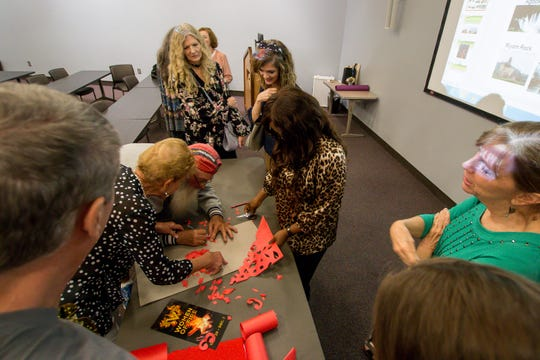 The Great Gulfcoast Arts Festival's Invited International Artist Abigail Nnaji, of Abuja, Nigeria, center, demonstrates how she uses the Chinese paper cutting technique during a presentation in the Anna Lamar Switzer Building at Pensacola State College on Tuesday, October 30, 2018.