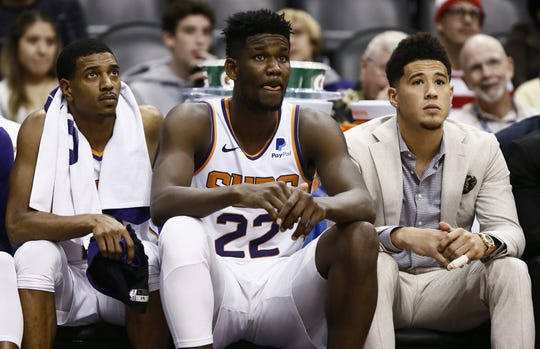 De'Anthony Melton, Deandre Ayton and Devin Booker sit on the bench during the Suns' 120-90 loss to the Spurs on Oct. 31.