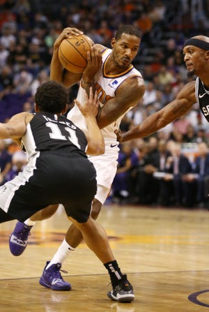 Suns forward Trevor Ariza drives to the basket against Spurs guard Bryn Forbes during the first half of a game Oct. 31 at Talking Stick Resort Arena.
