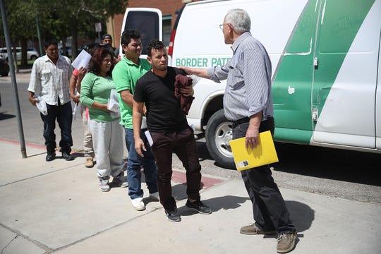 Inmigrantes son recibidos por autoridades mientras descienden de una camioneta de la Patrullla Fronteriza.