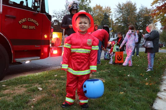 Ryker Stone, 3, dressed as a firefighter for Halloween, found a real fire truck during trick-or-treating in Port Clinton on Wednesday.