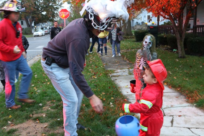 Ryker Stone, 3, dressed as a firefighter for Halloween, gets some candy from a real PCFD firefighter during Port Clinton's trick-or-treating in 2018.