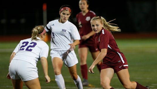 Arlington's Kendall Feighan looks to pass the ball away from Monroe-Woodbury's Kayla Bauer during Wednesday's class AA regional semifinal in Freedom Plains on October 31, 2018.