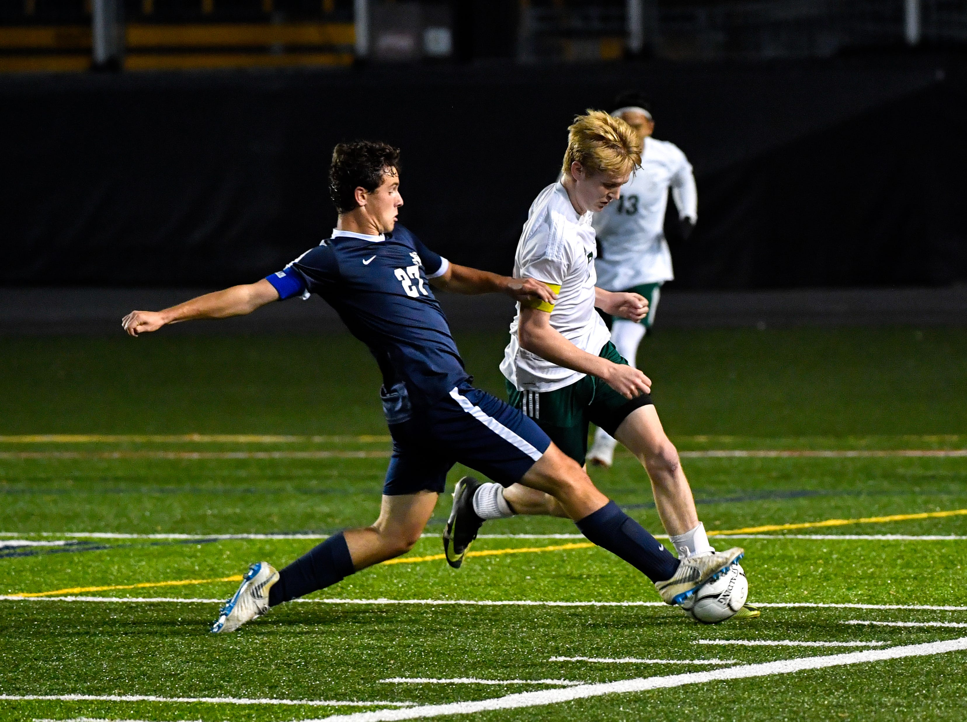 Camp Hill's Ben Brodie (27) slide tackles during the District 3 Class 1A boys' soccer finals between York Catholic and Camp Hill at Hersheypark Stadium, October 31, 2018. The Lions beat the Fighting Irish 2-0.