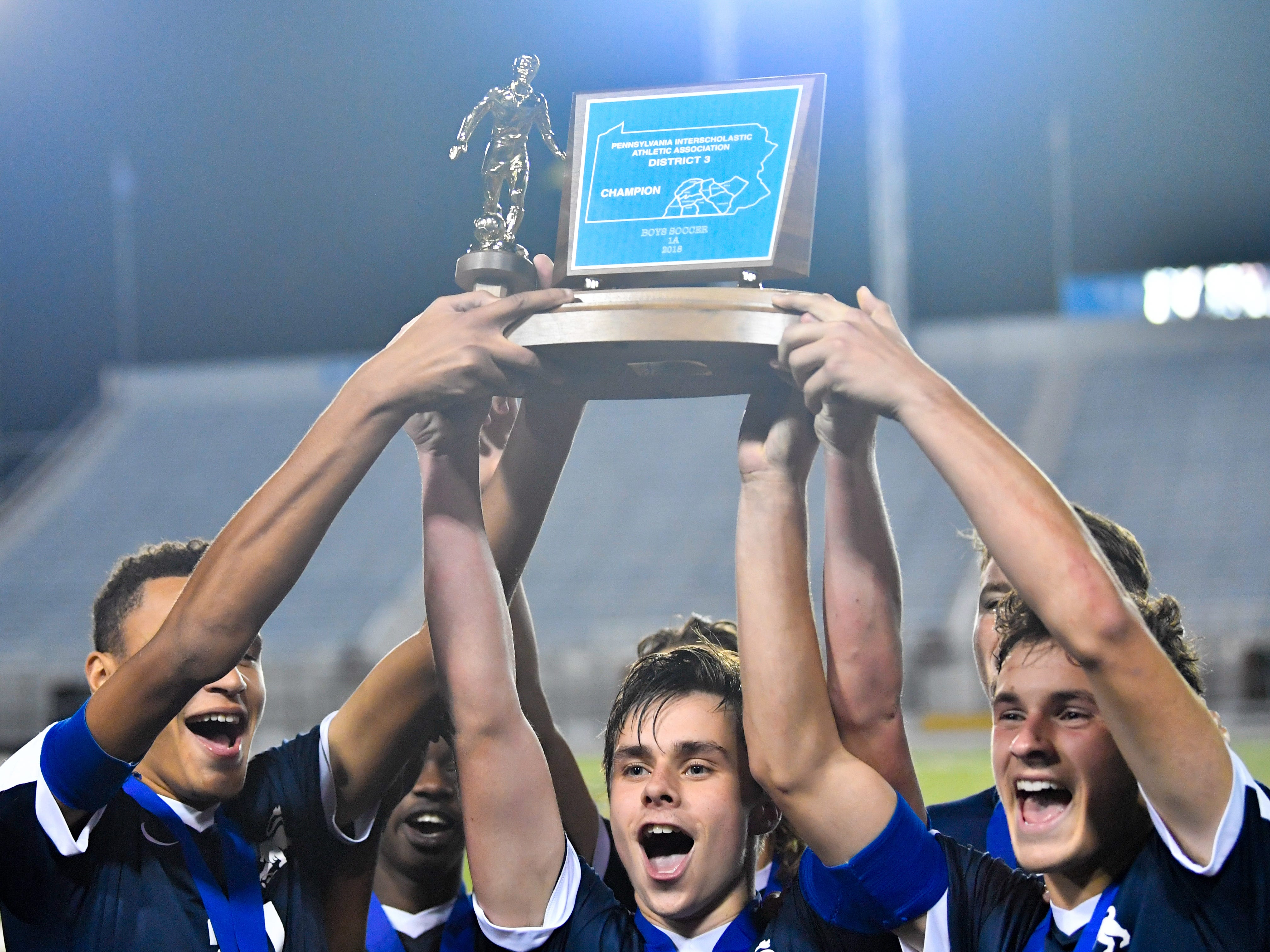 Camp Hill holds the District 3 Class 1A boys' soccer trophy up high at Hersheypark Stadium, October 31, 2018. The Lions beat the Fighting Irish 2-0.