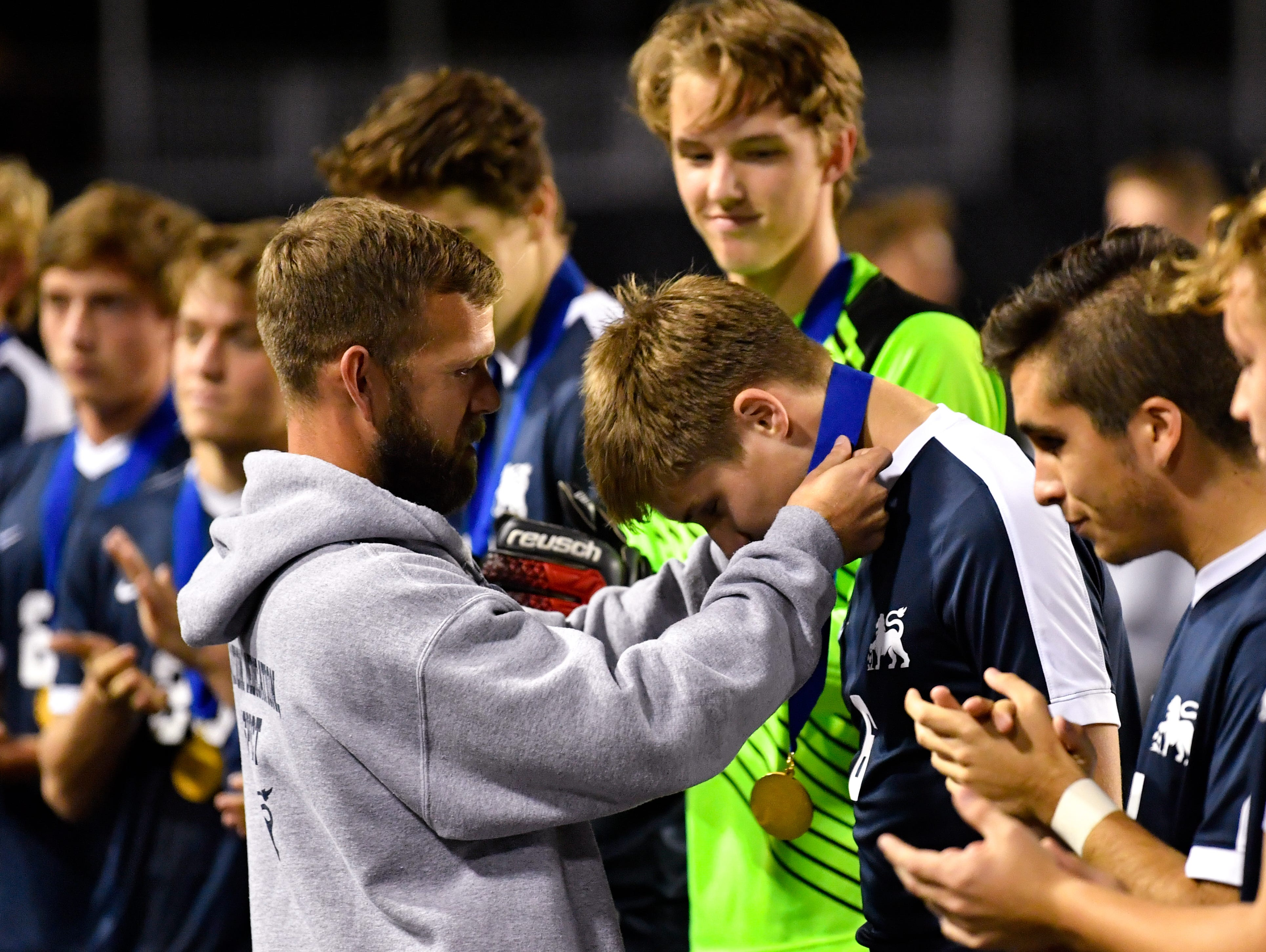Camp Hill coach Justin Sheaffer gives each player a first place medal after the District 3 Class 1A boys' soccer finals between York Catholic and Camp Hill at Hersheypark Stadium, October 31, 2018. The Lions beat the Fighting Irish 2-0.