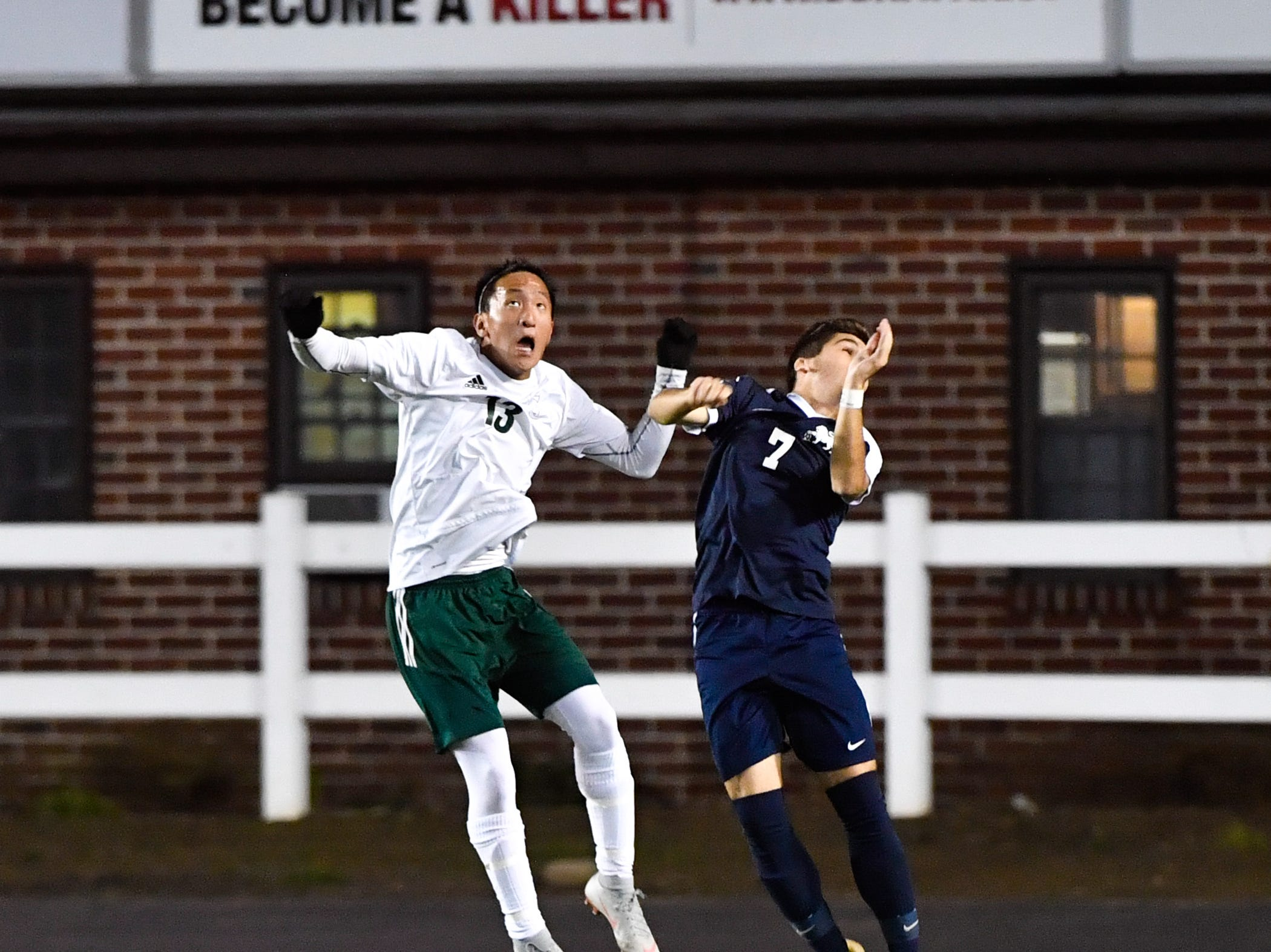 York Catholic's Sean Lavallee (13) and Camp Hill's Javier Gonzalez (7) go for the header during the District 3 Class 1A boys' soccer finals between York Catholic and Camp Hill at Hersheypark Stadium, October 31, 2018. The Lions beat the Fighting Irish 2-0.