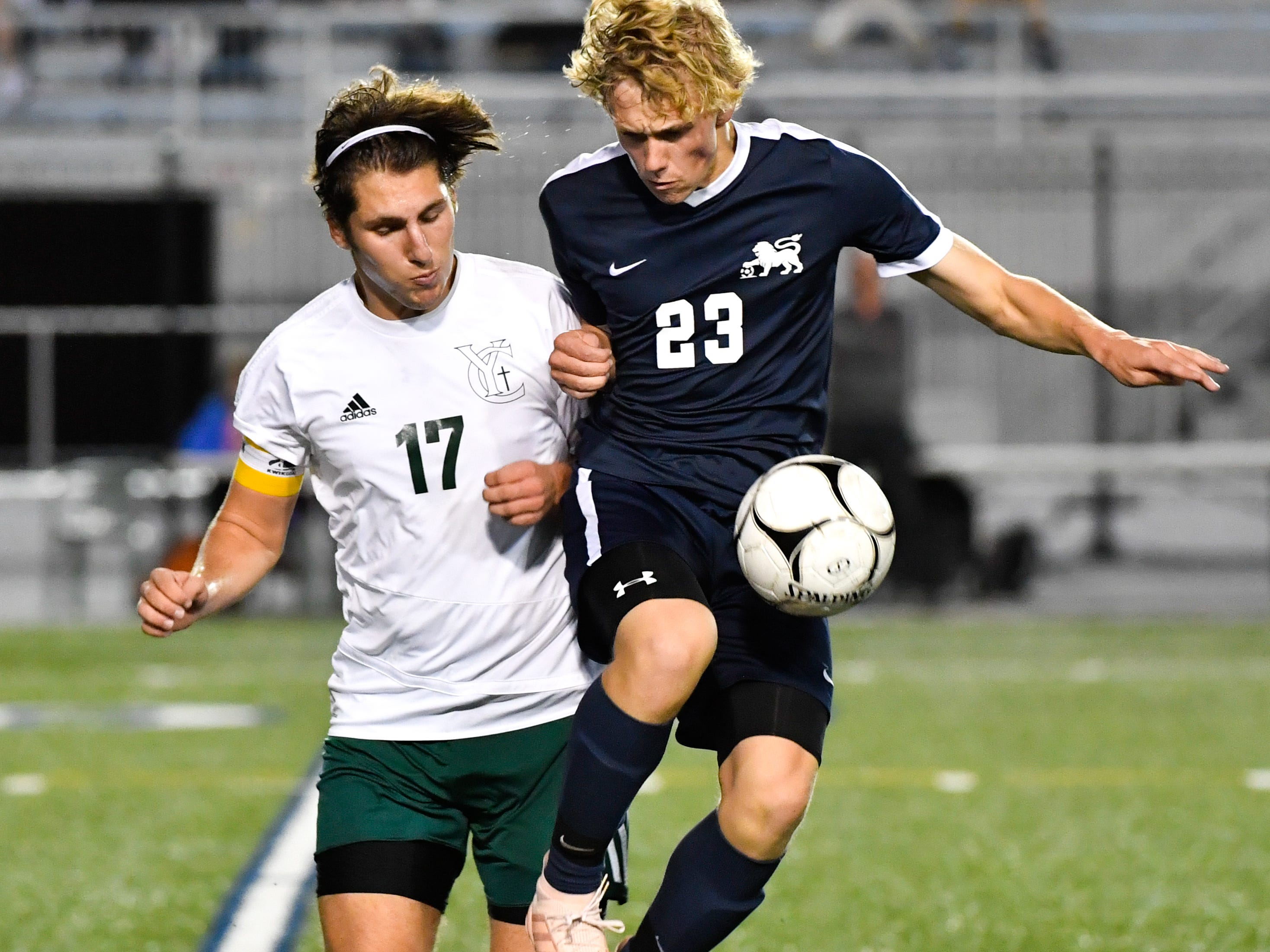 York Catholic's Nick Demarco (17) and Camp Hill's Kyle Pickering (23) fight to get the upper hand during the District 3 Class 1A boys' soccer finals between York Catholic and Camp Hill at Hersheypark Stadium, October 31, 2018. The Lions beat the Fighting Irish 2-0.
