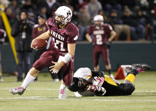 Aquinas quarterback Cory Benedetto, left, gets away from McQuaid's Derrick Members during a scramble during the 2011 Section V Class A football championship game.