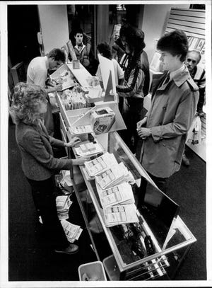 In 1984, store manager Barb Hayes assists a customer in Carhart Photo's new store in Midtown Plaza.