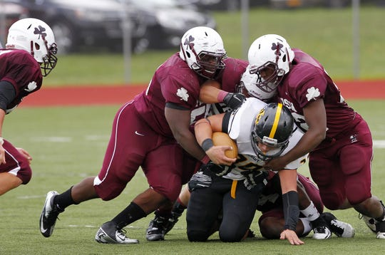 McQuaid's Cory Parker, center, is swallowed up by a sea of Aquinas' tacklers during football action between  McQuaid and Aquinas on Sept. 22, 2012. Aquinas won a defensive struggle 6-3.