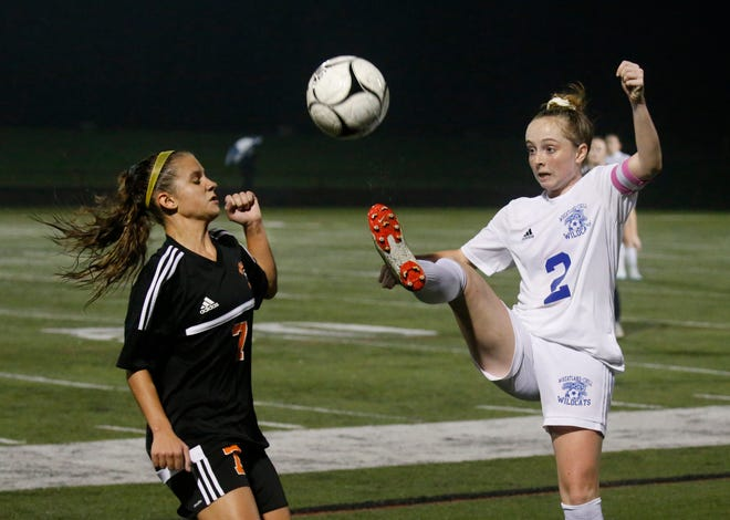 Marion's Angelina Gonzalez keeps a safe distance from Wheatland-Chili's Cassie Parker who raises her leg to take the ball in the first half of Wednesday's Class C qualifier at Penfield High School. Wheatland-Chili won 1-0.