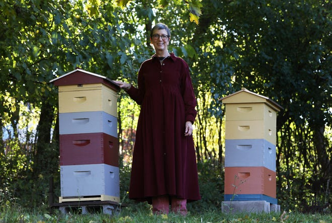 Elizabeth Agte in her Perinton backyard with her beehives. The town is considering drafting rules for beekeeping after receiving a complaint about the hives.