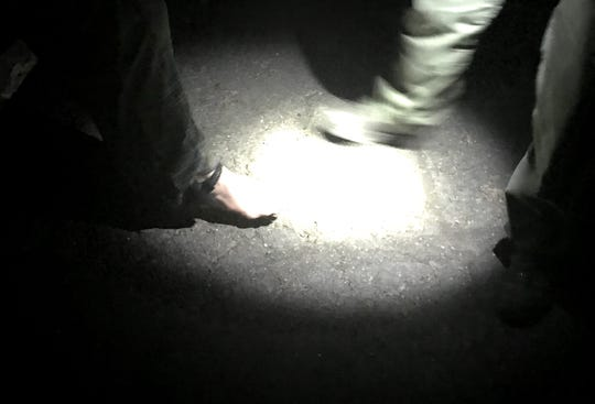 """Justin Benson, a parole agent with the California Department of Corrections, checks the ankle monitor of Jerry Pool, a convicted sex offender. As part of """"Operation Boo,"""" Benson and other law enforcement officials were checking to make sure convicted sex offenders in Redding were not offering candy to children or decorating their homes on Halloween."""