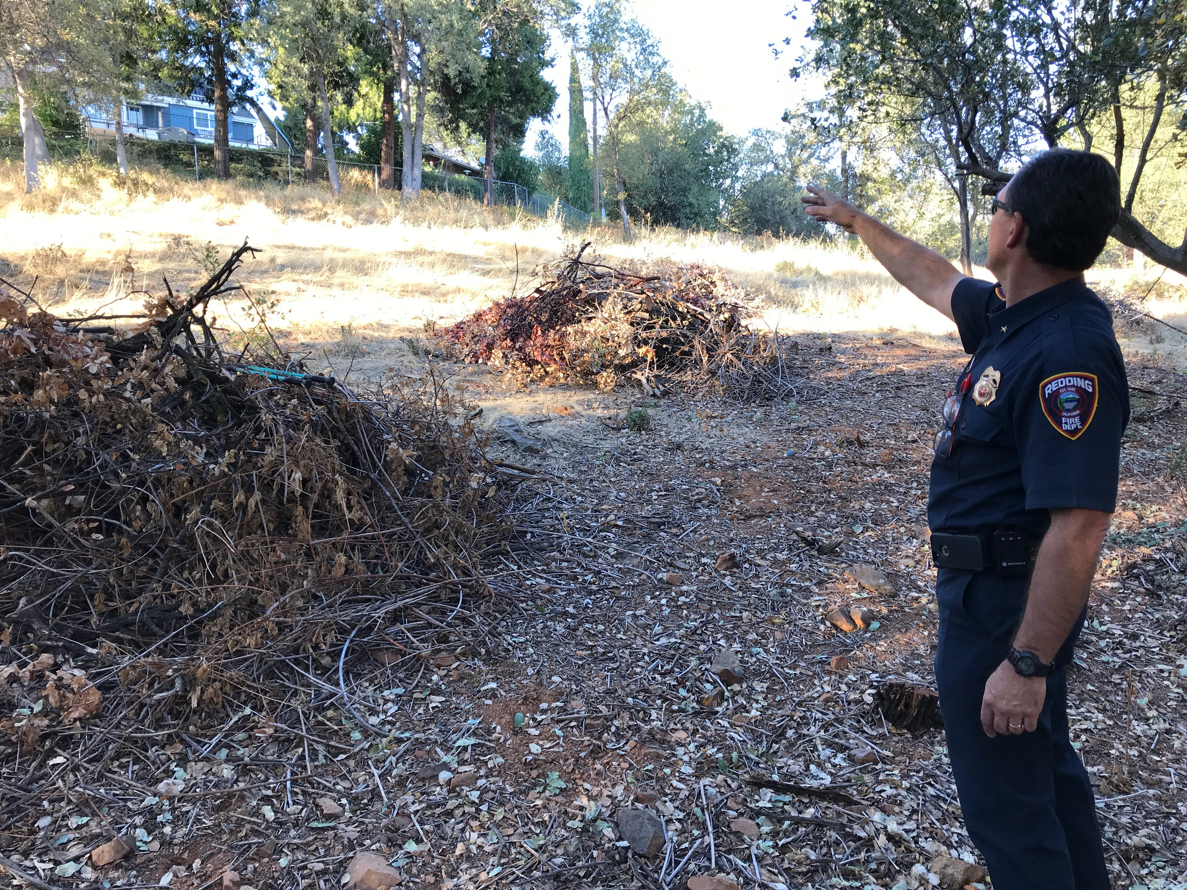 Redding Fire Marshal Craig Wittner points to a home off Royal Oaks Drive in the Sunset Terrace subdivision where an inmate fire crew collected and piled brush to reduce fire hazards in the 28-acre open space up to Arbor Place. The piles were going to be removed before another fuels-reduction project would take place on the north end of nearby Scenic Drive.