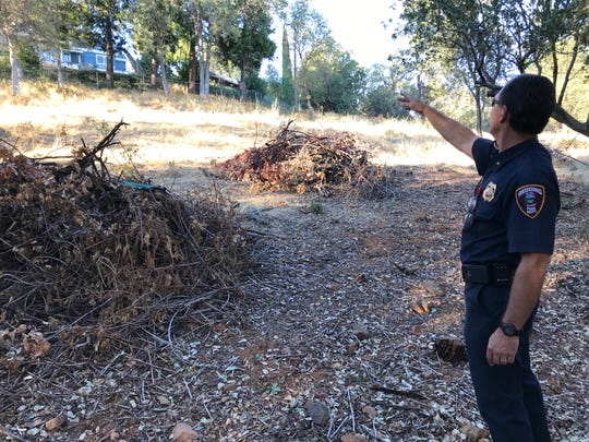 In November 2018, Redding Fire Marshal Craig Wittner points to a home off Royal Oaks Drive in the Sunset Terrace subdivision where an inmate fire crew collected and piled brush to reduce fire hazards in the 28-acre open space up to Arbor Place.