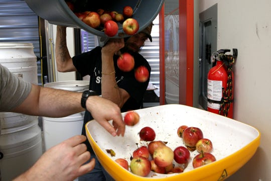 Divine Distillers workers demonstrate how him and his crew process apples to make their 2018 apple brandy on Wednesday, Oct. 31, 2018 at Divine Distillers.