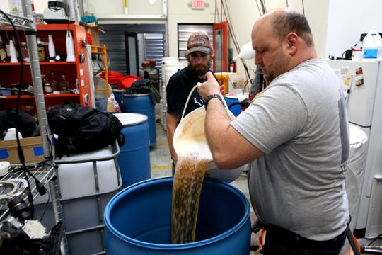 Divine Distillers owner, Jason Greenwood, pours fresh apple juice into a barrel to make their 2018 apple brandy on Wednesday, Oct. 31, 2018 at Divine Distillers.