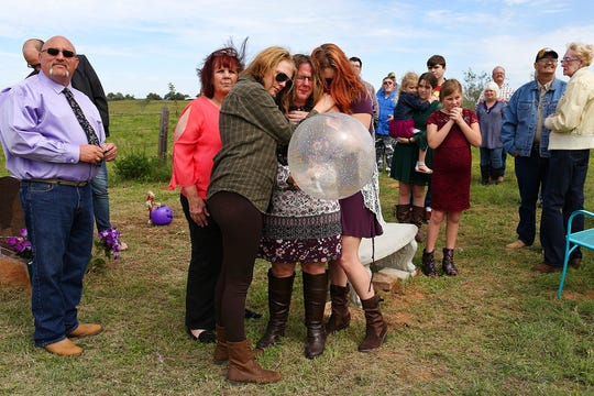 In this Oct. 21, 2018, photo, Sherri Pomeroy is embraced by her daugher-in-law, Chelsi Pomeroy, left, and her daughter, Kandi Pomeroy, right, as Sherri holds a balloon to release in honor of what would have been the 15th birthday for her slain daughter, Annabelle Pomeroy, in Sutherland Springs, Texas. Moments earlier, family and friends gathered with her at Annabelle's gravesite released balloons in different shades of purple, Annabelle's favorite color. At left is Annabelle's father, Frank Pomeroy.