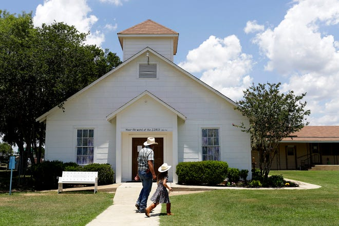 In this May 28, 2018 photo, Rod Green walks with his granddaughter, who was visiting from Colorado, as they visit the church in Sutherland Springs, Texas. Green and his wife, Judy, are long time members and run the church's food pantry that serves the community every Friday morning. (Lisa Krantz/The San Antonio Express-News via AP)
