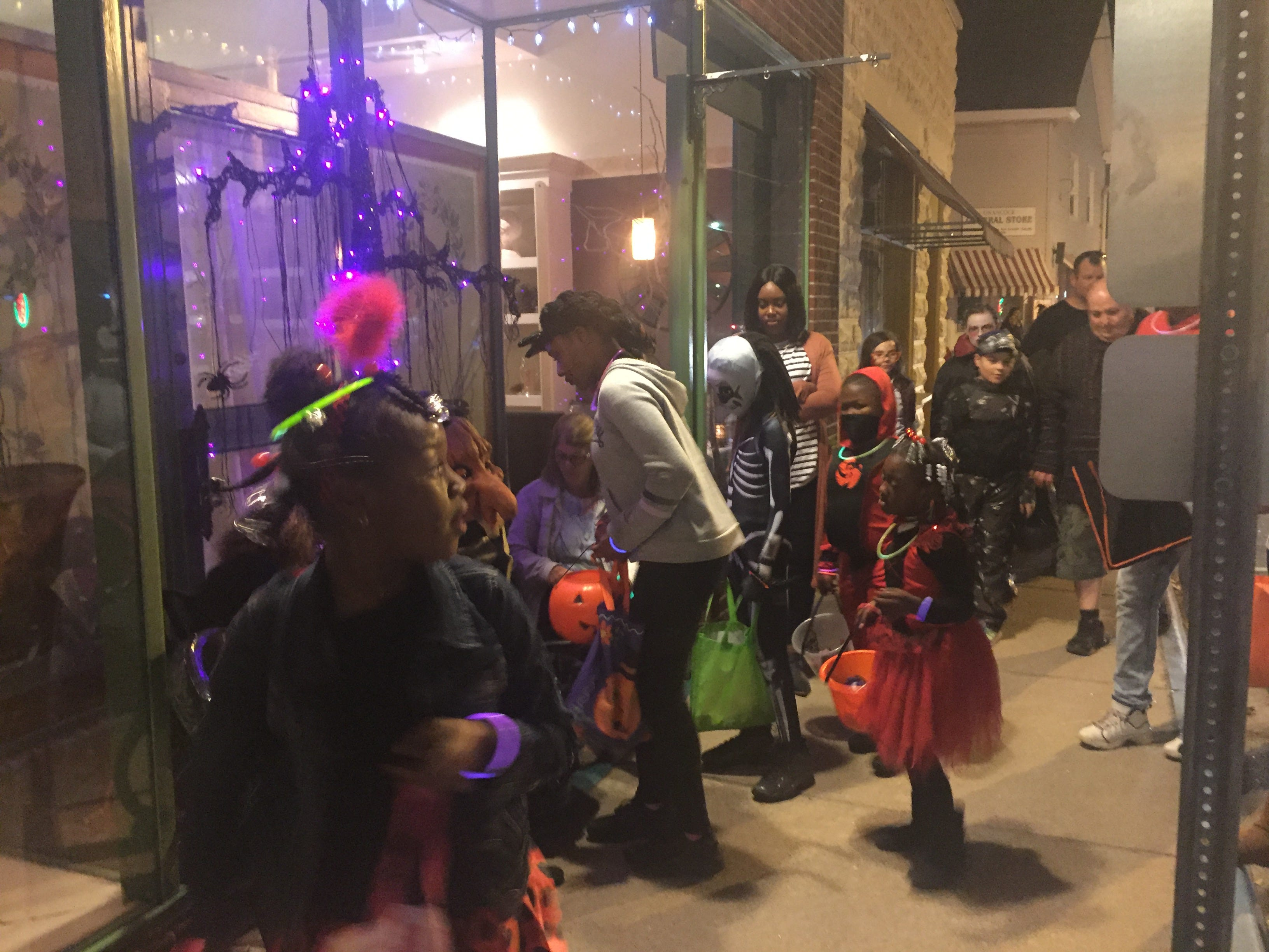 Volunteers pass out candy to trick-or-treaters outside the Charlotte Hotel in downtown Onancock on Wednesday, Oct. 31, 2018.