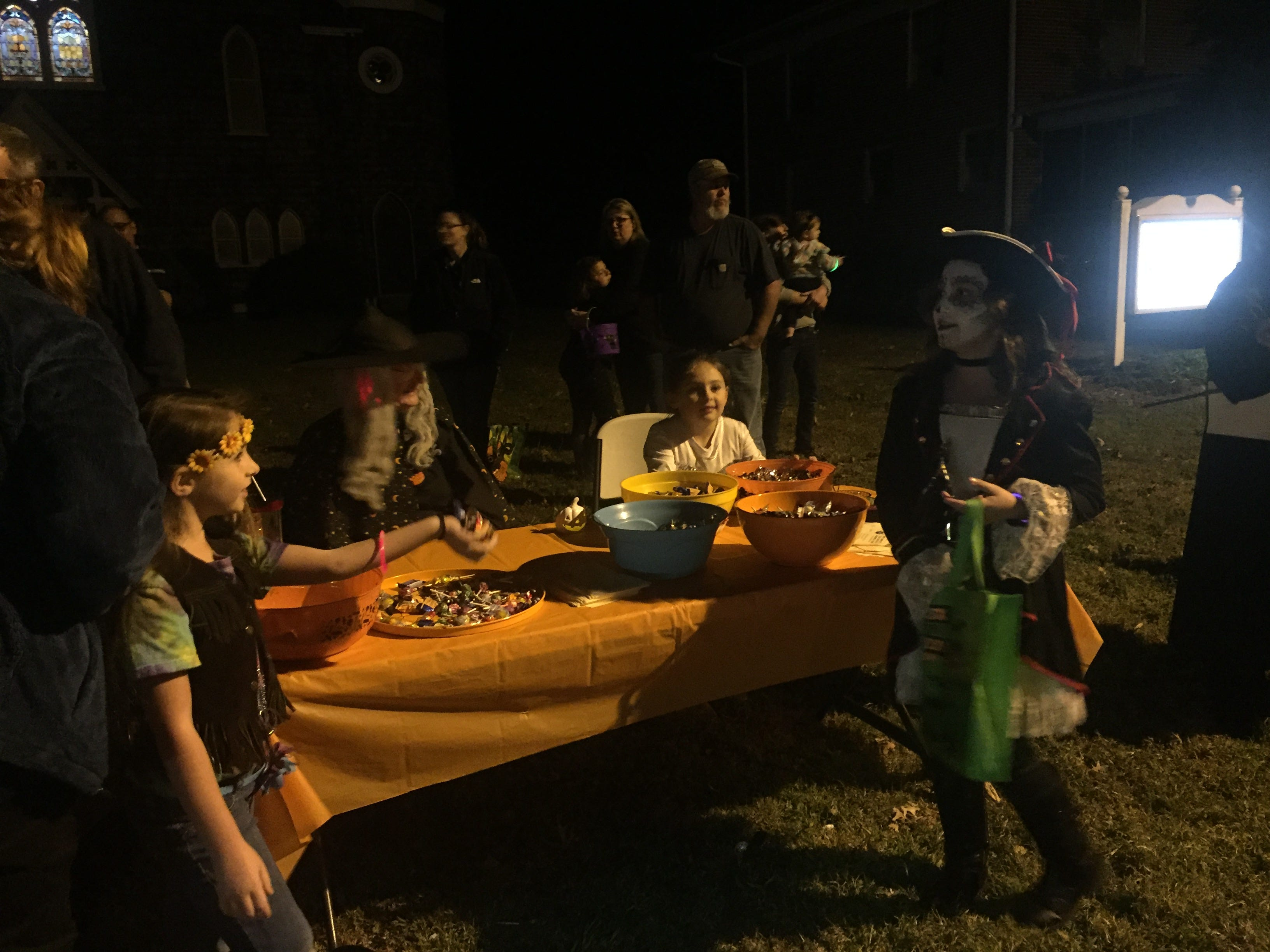 Volunteers at Market Street United Methodist Church in Onancock, Virginia pass out candy to trick-or-treaters on Wednesday, Oct. 31, 2018.