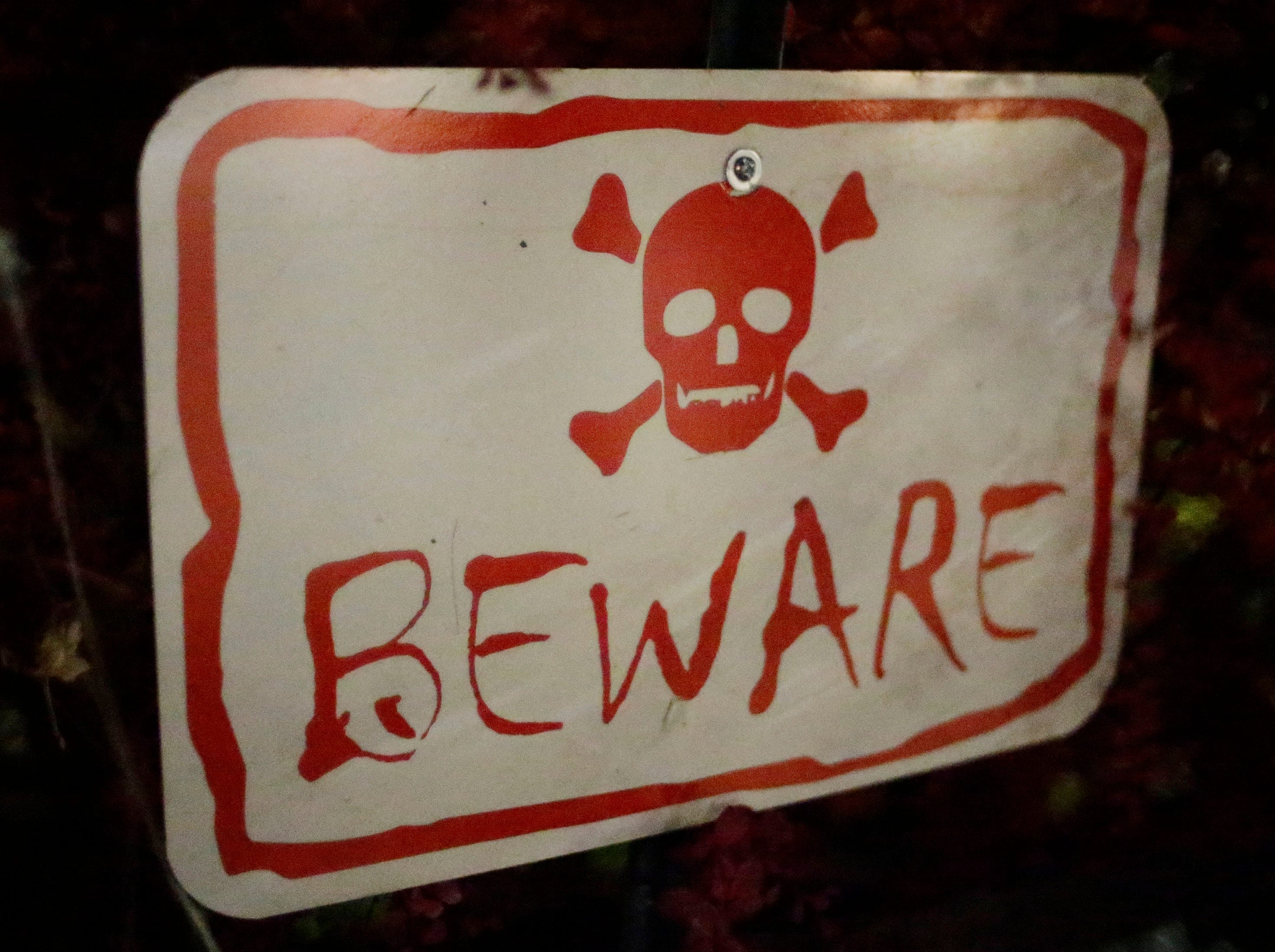 A sign warns visitors to Scott Grunert's haunted yard during Trick or Treat, Wednesday, October 31, 2018, in Sheboygan, Wis.