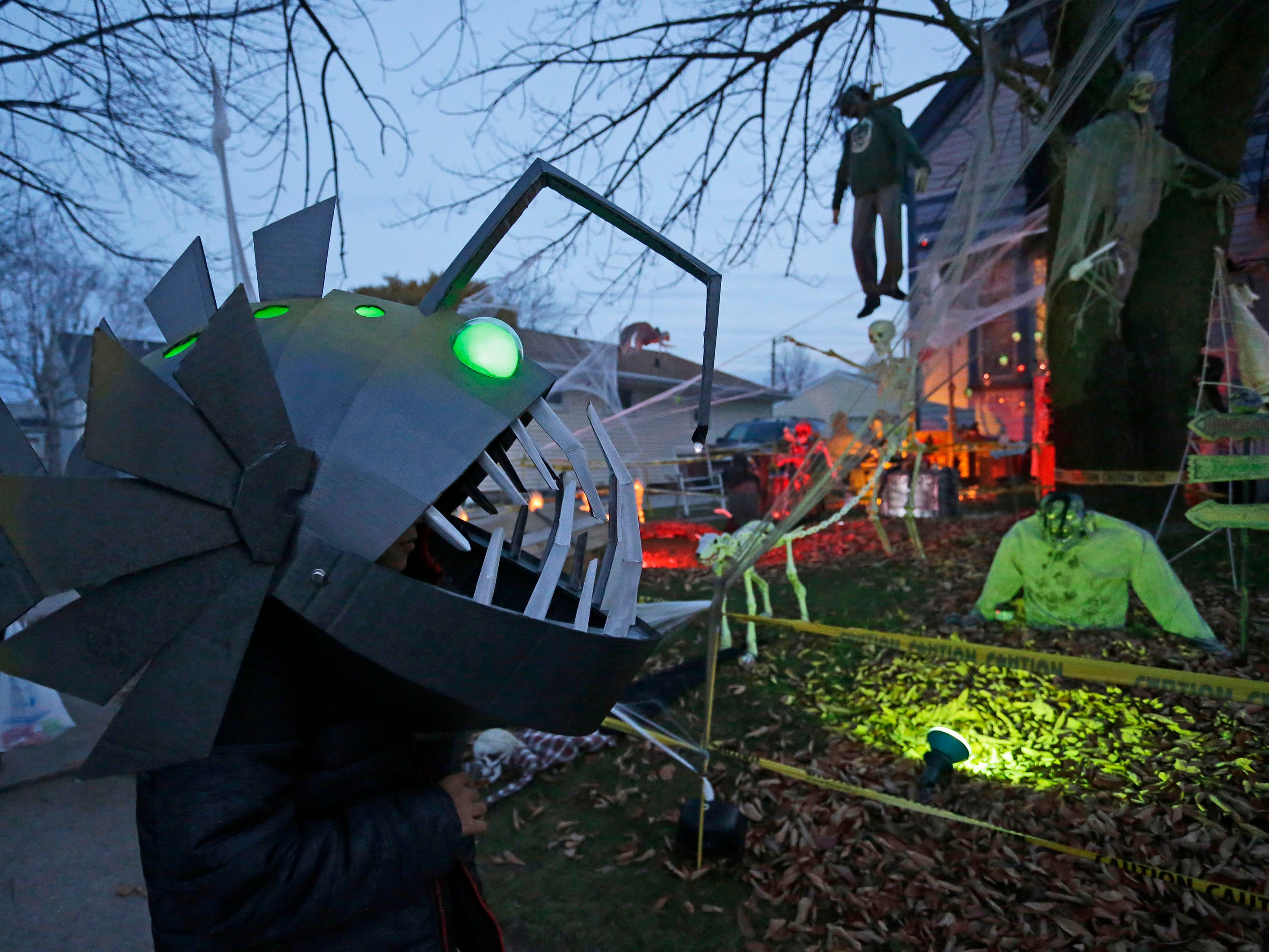 Wyatt Letourneau, 9, of Sheboygan, left, who is dressed as a Lantern Fish, is ready to scare during Trick or Treat, Wednesday, October 31, 2018, in Sheboygan, Wis.